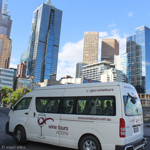 Wine tour van against Melbourne city skyline by Expat Edna